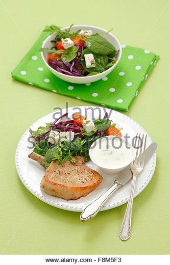 Ein Schweinekotelett mit einem Gemüsesalat, Feta-Käse und Joghurt-dip Stockbild