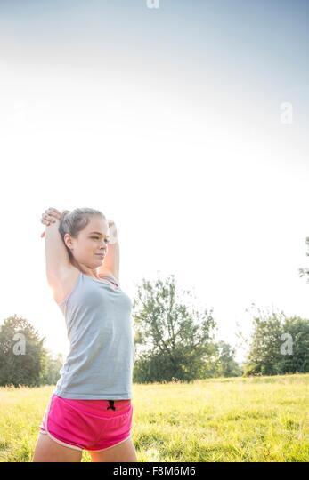 Junge Frau, Training, stretching, im Feld Stockbild
