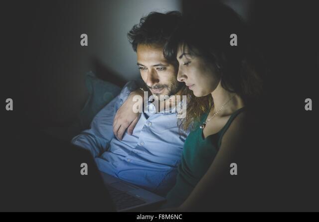Junge Frau sitzt mit Arm um den jungen Mann mit Laptop-Computer-Bildschirm beleuchtet Stockbild