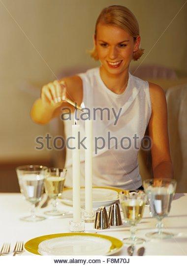 Eine junge Frau auf einem gedeckten Tisch eine Kerze anzünden Stockbild