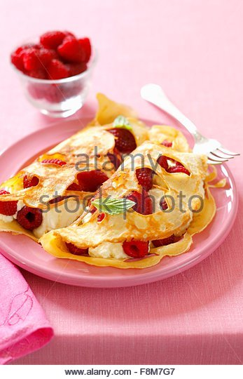 Löchrige Pfannkuchen mit Himbeeren und Sahne Stockbild