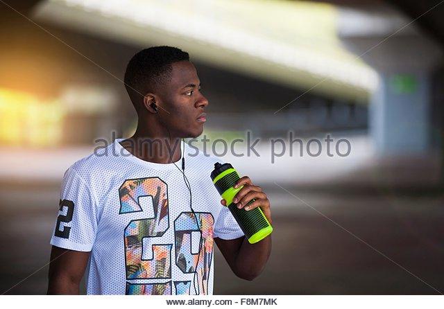 Junger Mann mit Wasserflasche, im freien Stockbild