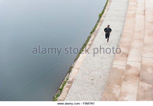 Junger Mann läuft neben Fluss, erhöht, Ansicht Stockbild