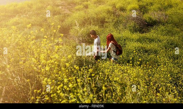 Aufnahme des jungen Paares zu Fuß durch Rasen auf einem Gipfel. Junger Mann und Frau Wandern an einem Sommertag. Stockbild