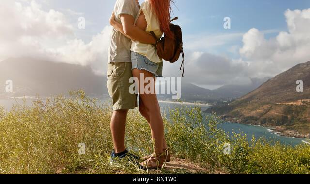 Bild des jungen Liebespaar stehend auf einer Klippe am Küste umarmt beschnitten. Niedrige Abschnitt Bild des Stockbild