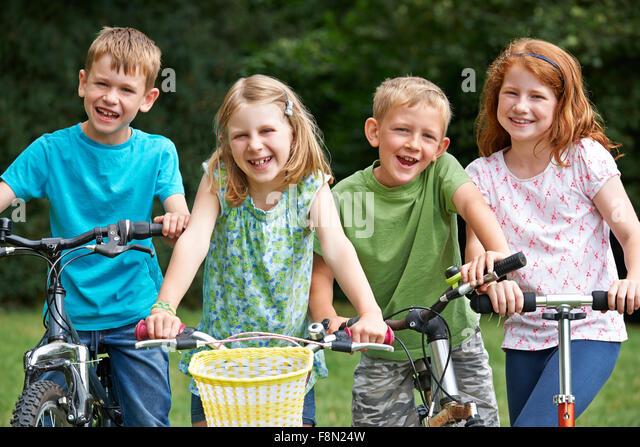 Gruppe von Kindern spielen auf Bikes und Scooter Stockbild