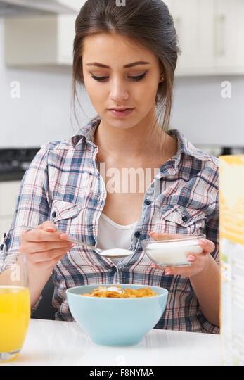 Teenagerin, die Zugabe von Zucker, Frühstücks-Cerealien Stockbild