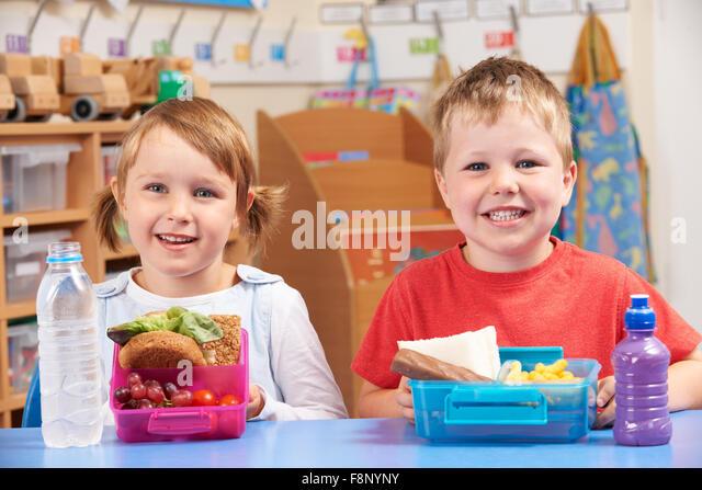 Grundschüler mit gesunden und ungesunden Mittagessen Boxen Stockbild