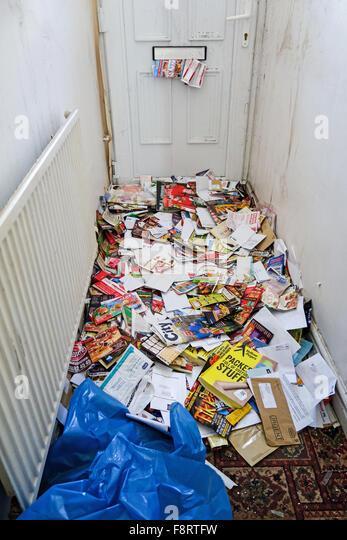 Viele Junk-Mails, Briefe und Broschüren und Flyer, durch einen Briefkasten ein leeres Haus Flur schaffen einen Stockbild