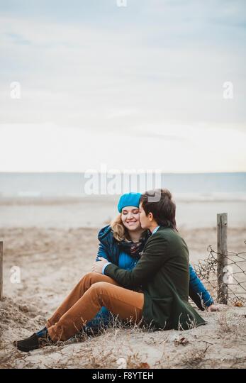 junges Paar sitzt und posiert am Strand im Herbst Stockbild