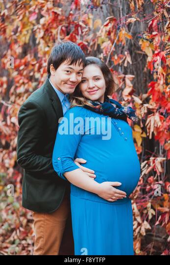 Schwangere Frau mit ihrem Mann posiert für die Kamera Stockbild