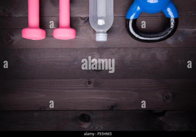 Sportgeräte. Blaue Wasserkocher Bell, Wasserflasche und rosa Hantel auf einem schwarzen Hintergrund aus Holz Stockbild