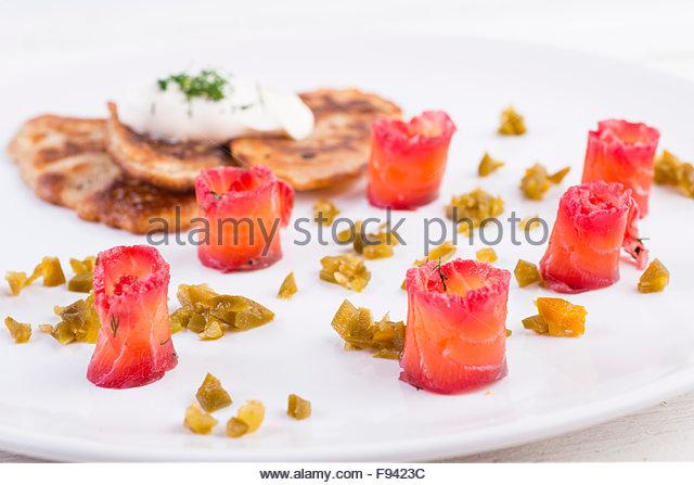 Graved Lachs (roher Lachs) mit Kartoffelpuffer, Jalapeño und Sauerrahm auf weißen Teller serviert Stockbild