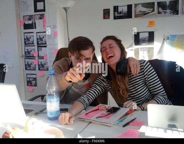 Fröhliche junge Frau mit Mann zeigte Sie In kreative Büro Stockbild