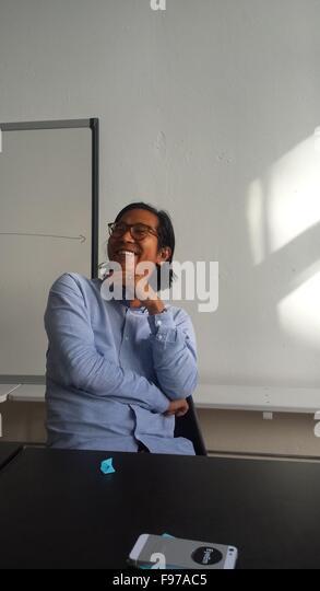 Lächelnd Mitte erwachsenen Mann sitzt im Klassenzimmer Stockbild