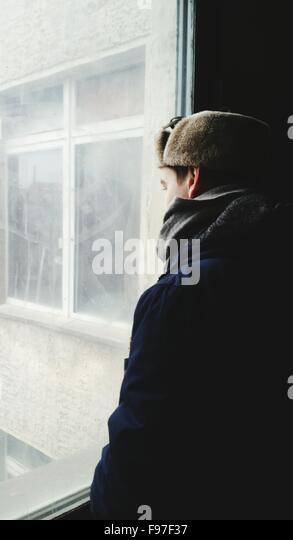 Mann auf der Suche durch Fenster im Gebäude Stockbild