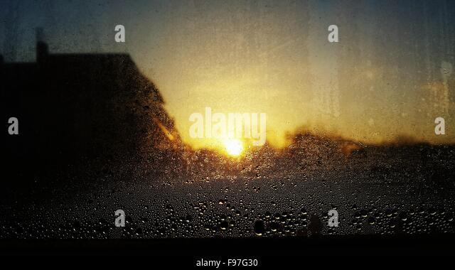 Nahaufnahme der nassen Glas gegen Himmel bei Sonnenuntergang Stockbild