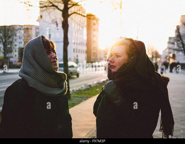 Junge Freundinnen stehen auf Straße In der Stadt Stockbild
