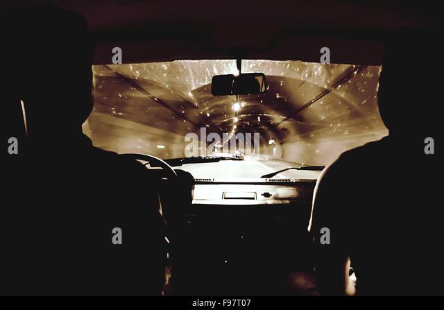 Silhouette Menschen fahren Auto In beleuchteten Tunnel Stockbild