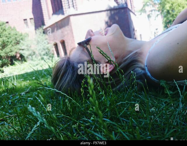 Seitenansicht der lächelnde Frau liegend auf dem Rasen im Park Stockbild