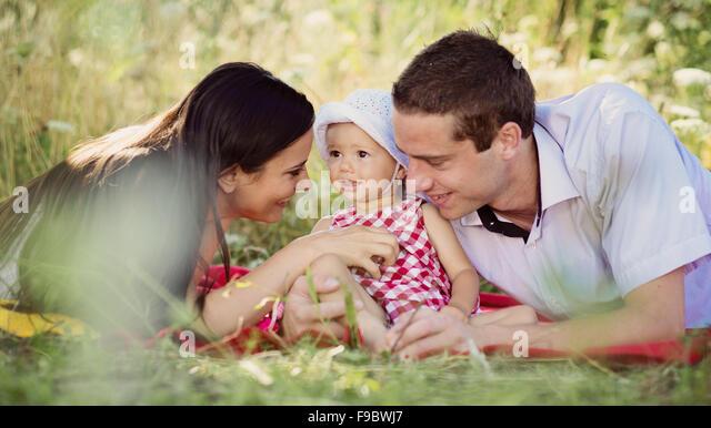 Glückliche junge Familie, die Zeit im Freien verbringen, an einem Sommertag Stockbild