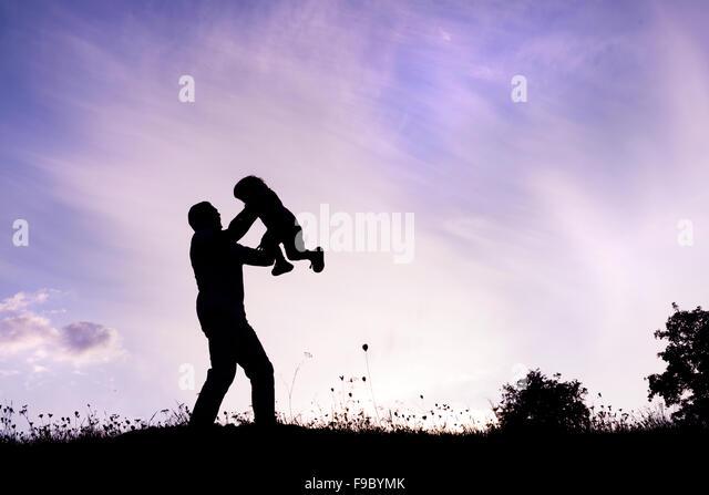 Silhouette der glückliche Vater mit seinem Sohn Spaß haben Stockbild
