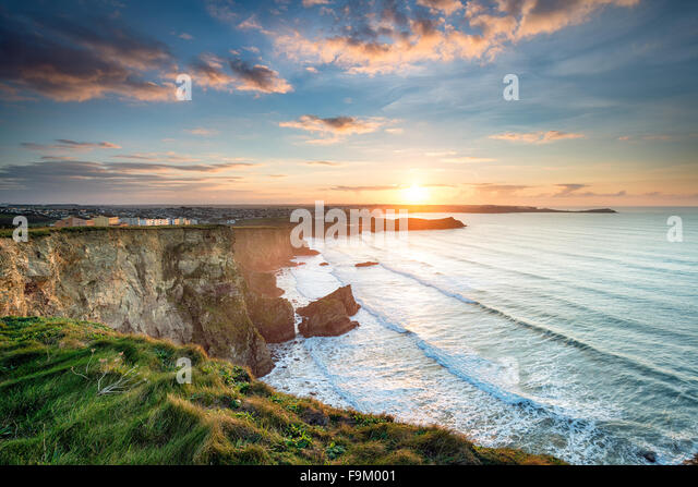 Atemberaubende dramatischen Sonnenuntergang von Klippen über Whipsiderry Strand von Porth in Newquay, Cornwall Stockbild
