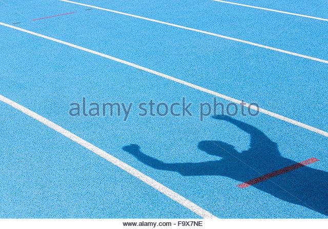 Tartanbahn und Schatten jubelnde Athleten Stockbild