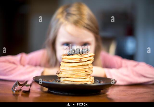 Platte mit Stapel von Pfannkuchen mit kleinen Mädchen im Hintergrund Stockbild