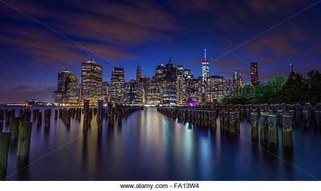 Eine beleuchtete Manhattan oder New Yorker Skyline bei Nacht mit dem Licht reflektiert in den Hudson River bei Langzeitbelichtung Stockbild