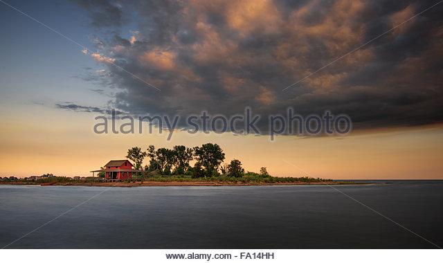 Guilford Grass Island mit seinen kultigen roten Hüttchen bei Sonnenuntergang mit einer riesigen Wolke drohend Stockbild