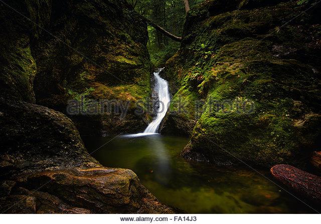 eine versteckte kleine Wasserfall und Bach im Wald oder im Wald von Connecticut, New England, umgeben von Felsen Stockbild