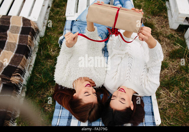 Mädchen liegen und packt ein Geschenk Stockbild