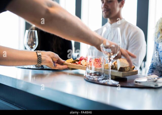 Zugeschnittenes Bild der Kellner servieren von Speisen an Kunden im restaurant Stockbild