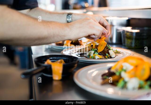 Zugeschnittenes Bild des Küchenchefs Gericht im Restaurant letzte Garnitur aufsetzen Stockbild