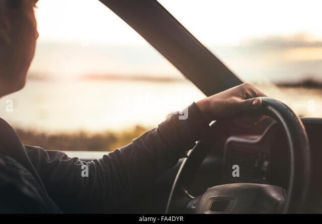 Zugeschnittenes Bild des Mannes betrachtet man Blick auf den Sonnenuntergang beim Auto fahren Stockbild
