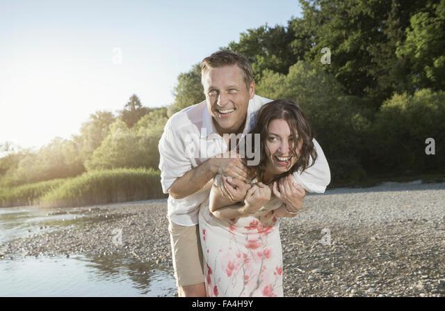 Reife Frau geben Huckepack Fahrt zu ihrem Mann am See, Bayern, Deutschland Stockbild