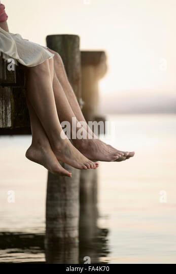 Paar Beine baumelt an Pier, Bayern, Deutschland Stockbild