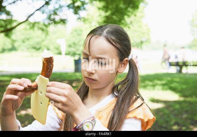 Mädchen, Einfügen von Wurst in Käse, München, Bayern, Deutschland Stockbild