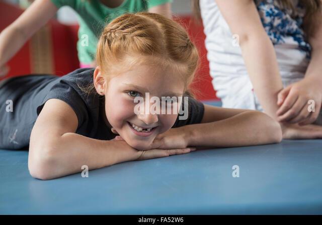 Mädchen liegend Gymnastikmatte in großen Turnhalle der Schule, Bayern, München, Deutschland Stockbild