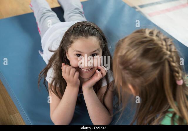 Mädchen liegend Gymnastikmatte Sport Hall, Bayern, München, Deutschland Stockbild