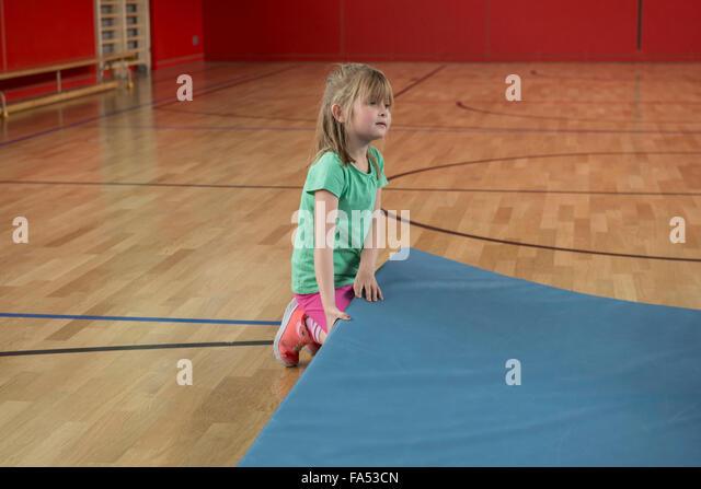 Mädchen versucht zu heben schwere Übung Matte in Basketballplatz Sporthalle, München, Bayern, Deutschland Stockbild