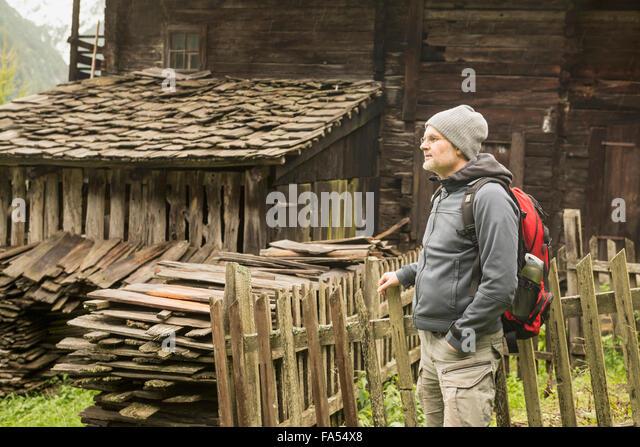 Reife Wanderer stehen in der Nähe von Hütte am regnerischen Tag, Österreichische Alpen, Kärnten, Stockbild