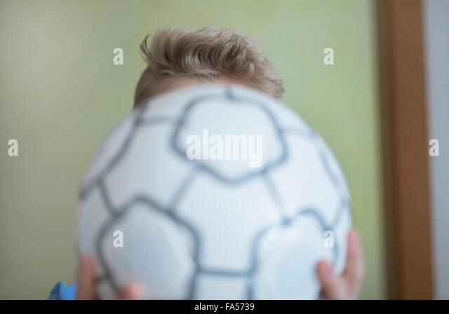 Junge hält Fußball vor seinem Gesicht, Freiburg Im Breisgau, Baden-Württemberg, Deutschland Stockbild