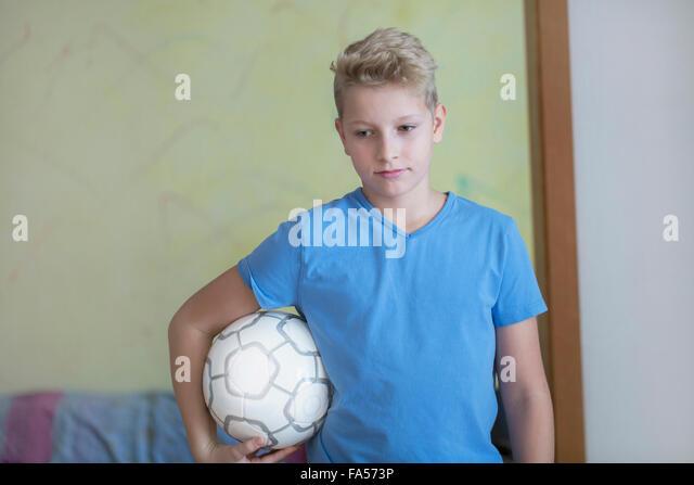 Jungen Fußball unter dem Arm hält und blickte, Freiburg Im Breisgau, Baden-Württemberg, Deutschland Stockbild