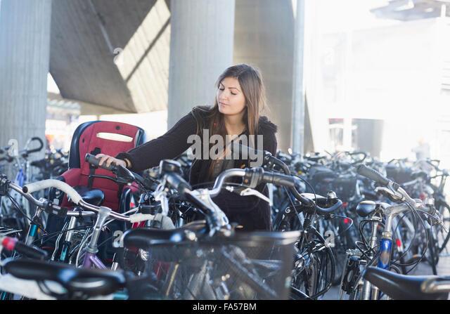Junge Frau, Parken ihr Fahrrad, Freiburg Im Breisgau, Baden-Württemberg, Deutschland Stockbild