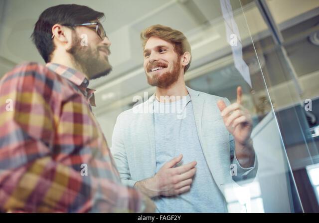 Glücklich Büroangestellte, die Noten der Tagung diskutieren Stockbild