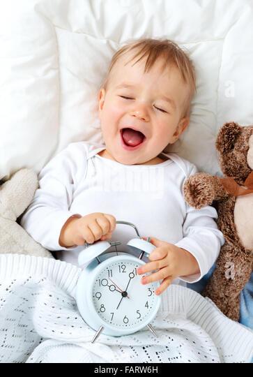 1 Jahr altes Baby mit Wecker Stockbild