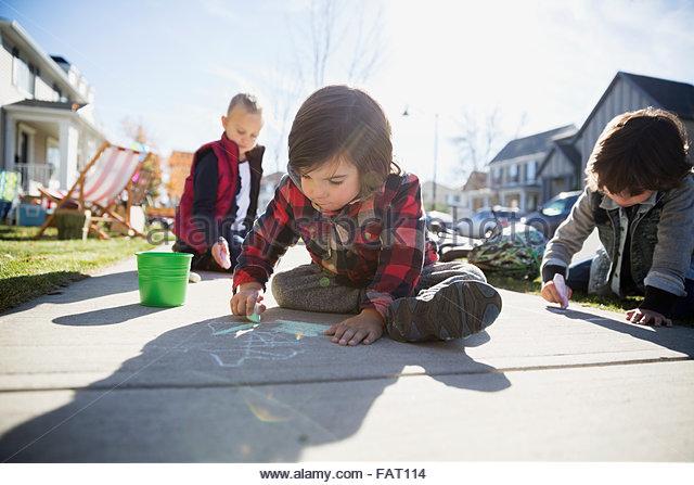 Kinder auf Bürgersteig mit Kreide Zeichnung Stockbild