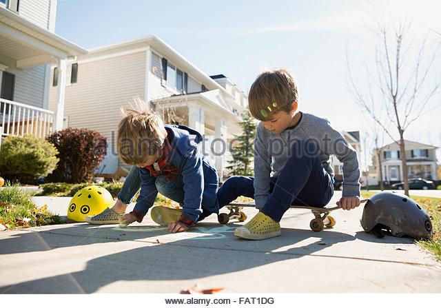 Brüder auf Nachbarschaft Bürgersteig mit Kreide zeichnen Stockbild